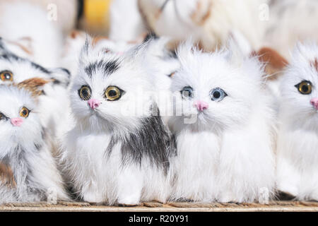 Soft toys kittens sitting in front of the camera - Stock Photo