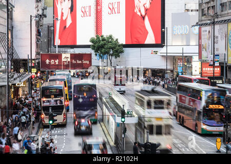 Hong Kong, China - May 16 2018: Tramway cars and buses rush in the crowded street of the famous Causeway Bay shopping district in Hong Kong island bus - Stock Photo