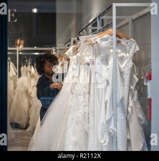 An employee arranges dresses in a David's Bridal store in the Chelsea neighborhood of New York on Sunday, November 11, 2018. David's Bridal is reported to be preparing a Chapter 11 bankruptcy filing if it cannot reach a deal with its creditors. The company has until November 14 to make the interest payment on its approximately $760 million in debt.  (© Richard B. Levine) - Stock Photo