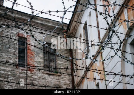 Old ramshackle decrepit walls of soviet prison through barbed wire fence. Old Soviet prison Patarei, Russian fortress Defence Barracks and museum in T - Stock Photo