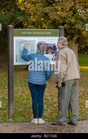 a tourist information board at Holkham park, Holkham hall in Norfolk with a couple or husband and wife getting directions looking at a map. - Stock Photo