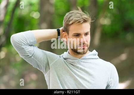 Man confident in his antiperspirant. Guy checks dry armpit satisfied with clean clothes. Sportsman after training pleased with antiperspirant. Prevent, reduce perspiration. No sweat - deodorant works. - Stock Photo