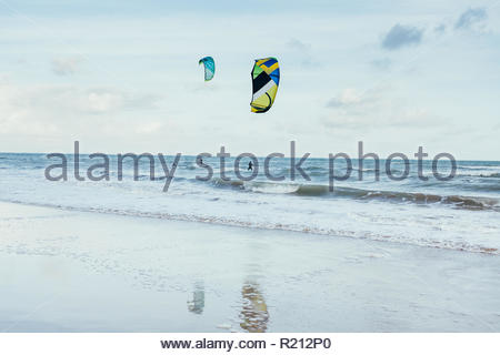 Kitesurfing sails and their reflections on the water of the beach - Stock Photo