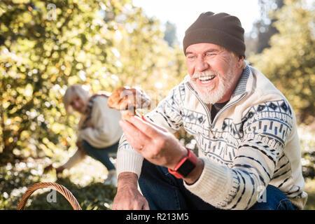 Pleasant cheerful aged man looking at the mushroom - Stock Photo
