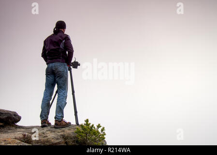 Outdoor photographer with tripod and camera on rock thinking. Thick fog in autumnal countryside. Man work on sharp clif. - Stock Photo