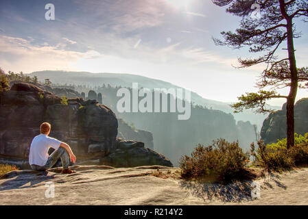 Man sitting on the rock in mountain and watching sunrise. - Stock Photo