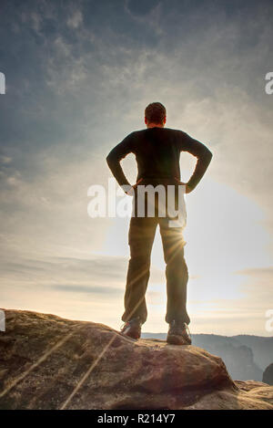 Lone figure watches the sunrise from sharp rock looking down at the wild landscape - Stock Photo