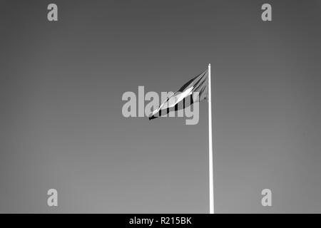 A United Arab Emirates flag flying against clean and tranquil sky. UAE celebrates it's national day on 2nd December every year. - Stock Photo