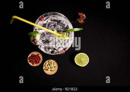 tasty and fresh gin and tonic cocktail on a black background next to your ingredients - Stock Photo