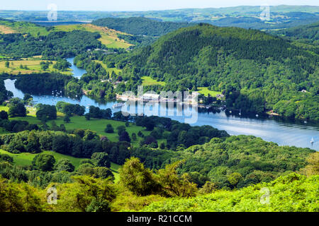 The view over south end of Lake Windermere from the path to Gummers How on a beautiful summer morning. A passenger ferry arrives at Lakeside pier. Gummers How is a well known viewpoint in The Lake District, Cumbria, UK. - Stock Photo