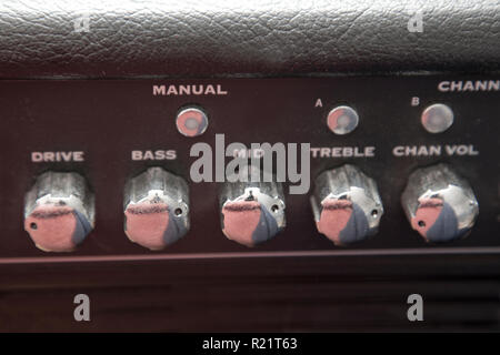 Dials that set the range and channel for a guitar amplifier - Stock Photo