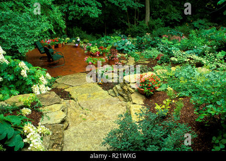 Stone steps lead down to private shade garden and brick patio with chairs and blooming flowers, Midwest