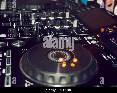 Sound mixing console detail, close up. DJ professional music console. Wide angle photo of black sound mixer controller with knobs and sliders. Professional audio mixing console with faders and adjusting knob. - Stock Photo