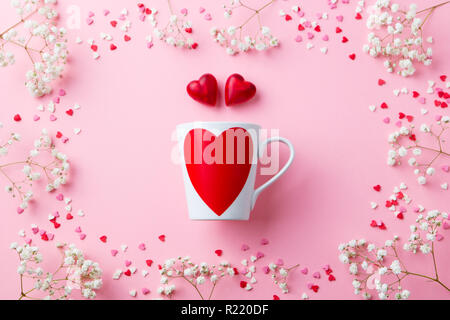 Mug with heart with sugar and chocolate hearts. Pink background. Flat lay composition. Top view. - Stock Photo