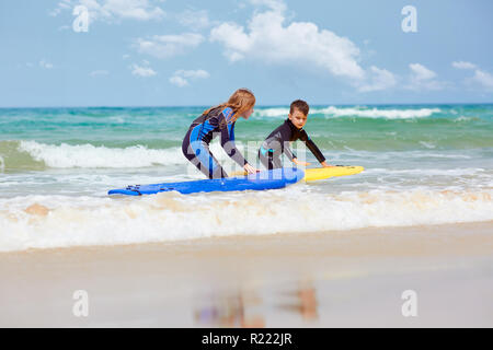 Kids with surfboards near sea - Stock Photo
