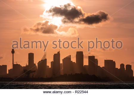 The skyline of Sydney as seen from Sydney Harbour in evening backlight. - Stock Photo