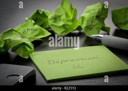 Depression. The word 'depression' is written on green sticky note on wooden black table. Crumpled green sticky notes are scattered with texts written - Stock Photo