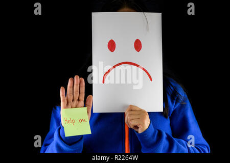 A depressed woman in a blue sweater covering and hiding her face with a white cardboard with a sad face drawing sign with Help me text on sticky note. - Stock Photo