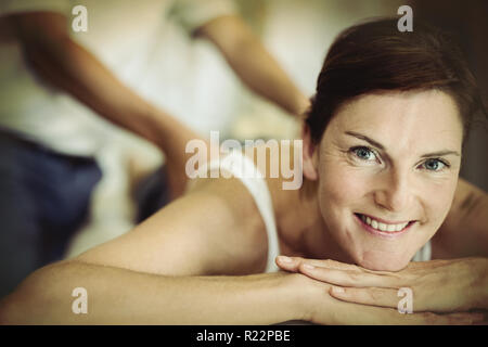 Woman receiving back massage from physiotherapist - Stock Photo
