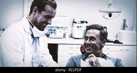 Dentist discussing over digital tablet with male patient - Stock Photo