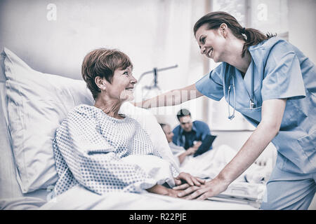 Nurse consoling a patient in hospital ward