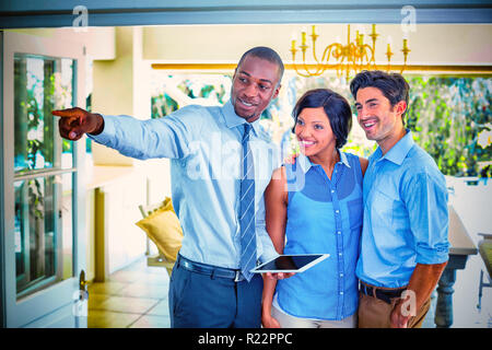 Real estate agent showing house to couple - Stock Photo