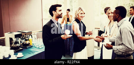 Business executives interacting with each other while having coffee - Stock Photo