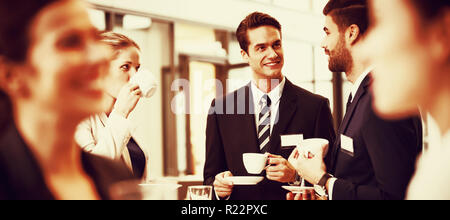 Businesspeople interacting with each other while having coffee - Stock Photo