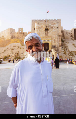 Aleppo, Aleppo Governorate, Syria : An old man stands outside the Citadel of Aleppo a large medieval fortified palace in the centre of the old city. - Stock Photo