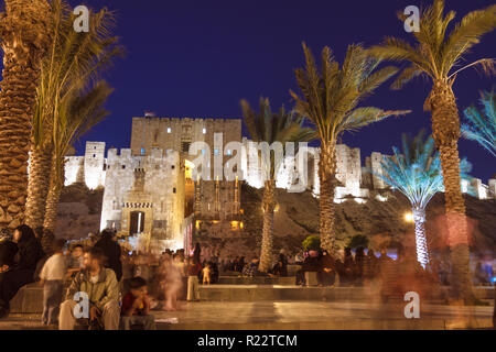 Aleppo, Aleppo Governorate, Syria : People sit outside the Illuminated Citadel of Aleppo, a large medieval fortified palace in the centre of the old c - Stock Photo