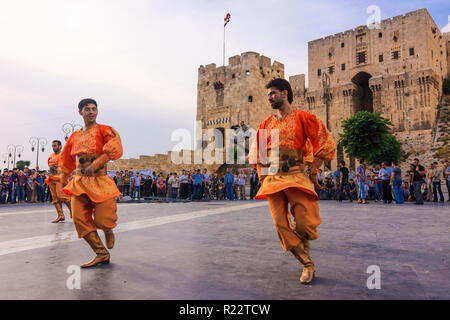 Aleppo, Aleppo Governorate, Syria : Men in traditional costumes dance by the citadel of Aleppo. - Stock Photo