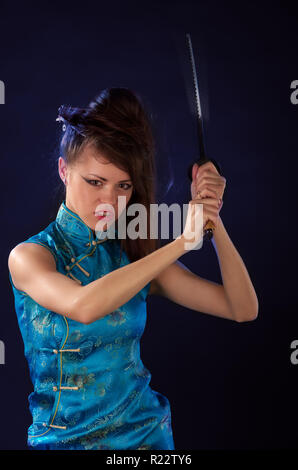 Beautiful girl dressed in a traditional dress with katana in her hands - Stock Photo