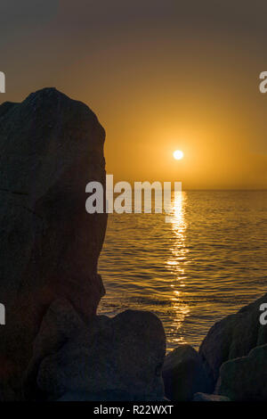 The setting sun is reflected on the sea near the rocky coast of Pacific Grove, California. - Stock Photo