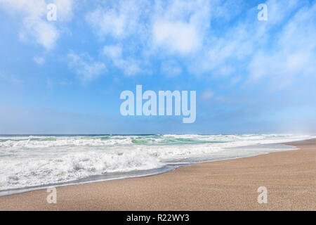 Gentle waves break on a sandy beach under a cloudy blue summer sky along California's Point Reyes National Seashore. - Stock Photo