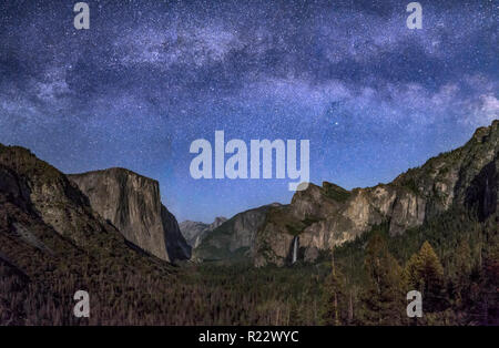 Yosemite Valley, from Tunnel View, is softly illuminated by the setting moon with the Milky Way above. - Stock Photo
