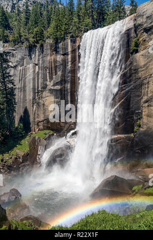 The wet, misty spray surrounding Vernal Falls, on the Merced River in California's Yosemite National Park, makes for colorful rainbows on a summer sum - Stock Photo