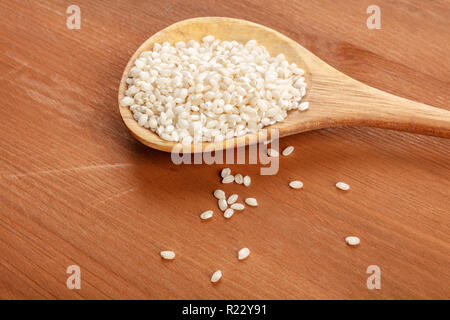 A closeup photo of Spanish calasparra rice used for paella in a wooden spoon on a rustic background with copy space - Stock Photo