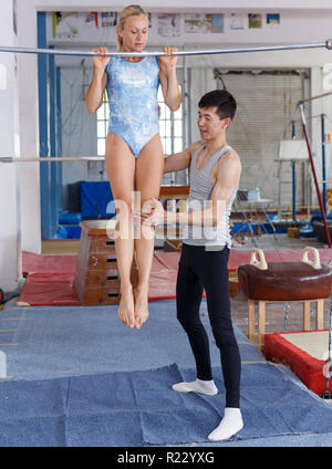Fit man and woman doing acrobatic exercises in gym securing each other - Stock Photo