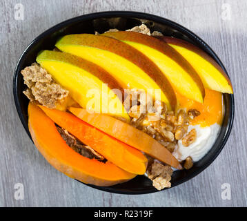 Breakfast with pumpkin and mango. Pumpkin slices bake in the oven, cut mango. Oat flakes, whipped cream, dried fruits put on plate with pumpkin and ma - Stock Photo