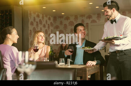 Polite smiling young waiter bringing ordered dishes to guests at restaurant - Stock Photo