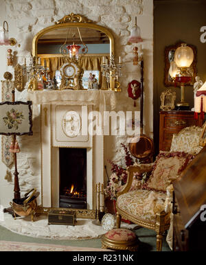 Vintage firescreen beside fireplace in Victorian style sitting room - Stock Photo