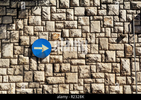 Traffic sign one way street sign with an arrow on a stone wall is a pattern of texture and material with colored stones / Old brick wall as background - Stock Photo