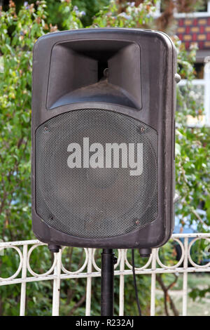 Black big speaker on stand outdoor / A big p.a. speaker on a stage at an outdoor music festival / Large audio speaker and equipment / Urban city. - Stock Photo