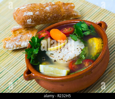 Cod fish soup recipe. Make broth from head of hake, merluccius or other cod-like fish. Add potatoes, carrots, corn, shallots, 200 gr fish steak, salt, - Stock Photo