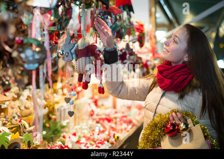 Smiling young woman choosing decorations for Christmas tree at market in evening - Stock Photo