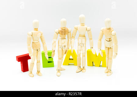 Wooden figures posing as business men in front of the word TEAM, isolated on white. Team, unity and collaboration concept - Stock Photo