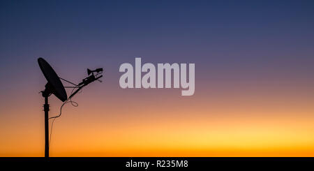 Satellite silhouetted against golden sky at sunset - Stock Photo