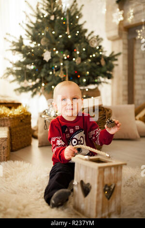 Child boy is sitting on the carpet and playing against the background of the Christmas tree, festive garlands and gift boxes. - Stock Photo