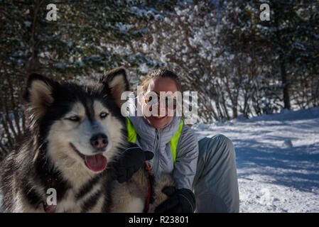 Girl with husky dog in the snowy mountains on a bright sunny day - Stock Photo