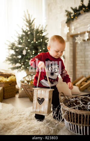 Child boy is standing on the carpet and playing against the background of the Christmas tree, festive garlands and gift boxes. - Stock Photo